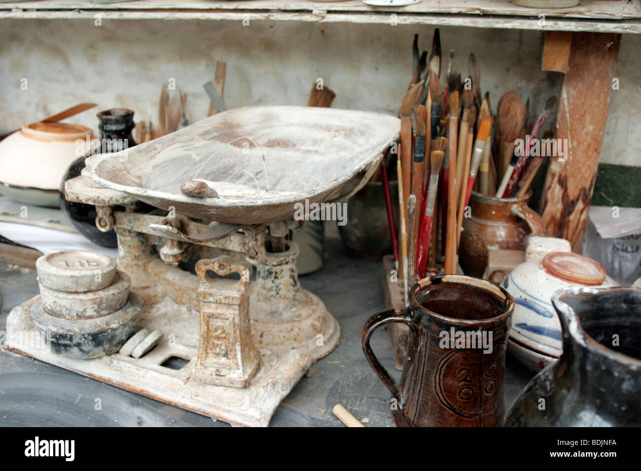 A potter's tools including weighing scales, brushes and examples of work - Stock Image