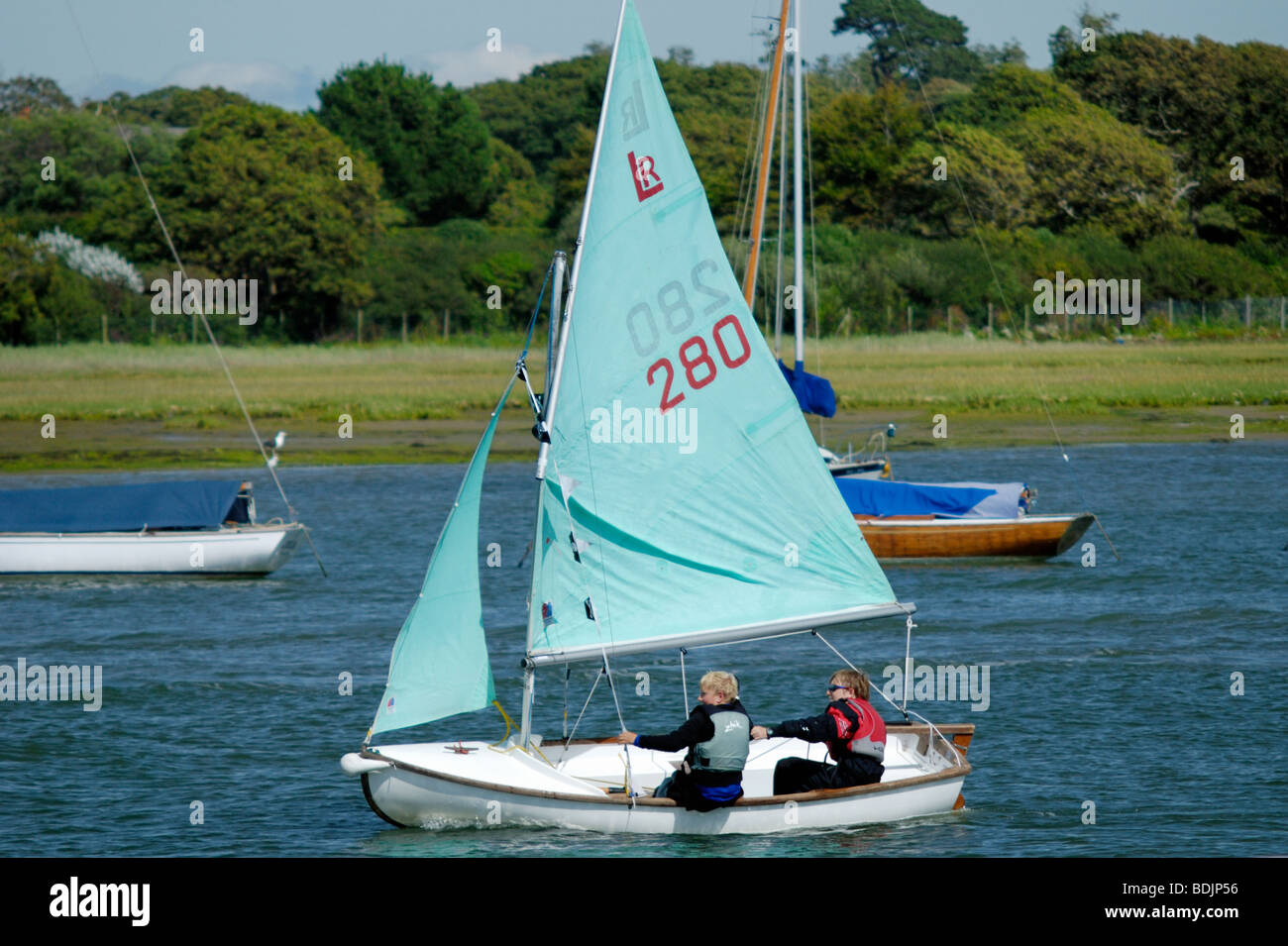 Two children sailing in a dingy - Stock Image