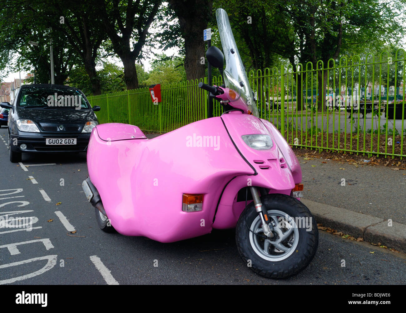 A pink disability scooter parked in a disabled bay - Stock Image