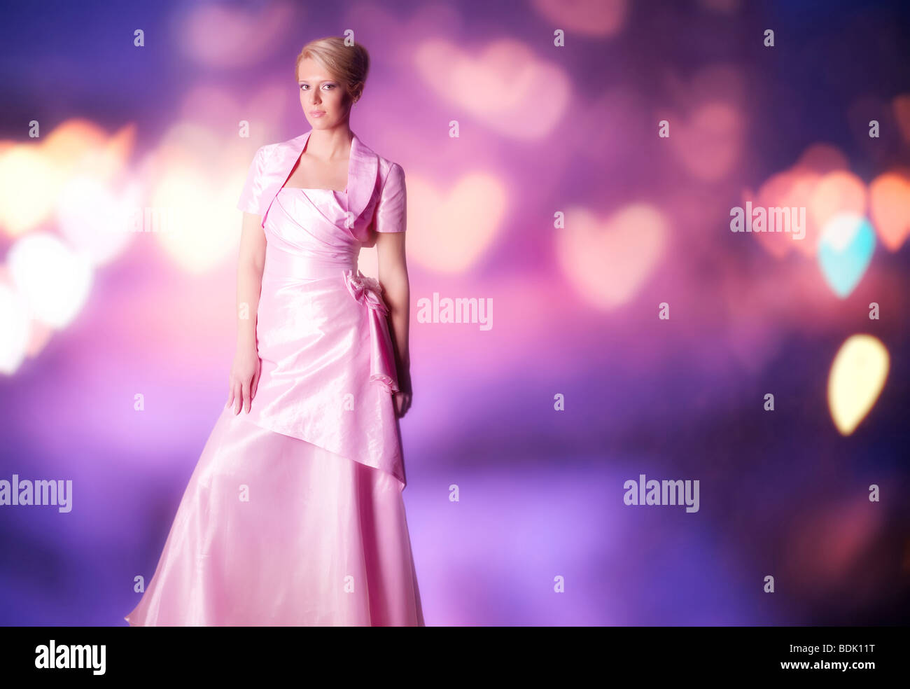 Woman in pink dress on abstract blurry background. - Stock Image