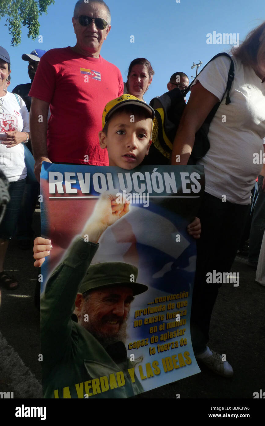 Young boy holding a poster celebrating the Cuban revolution at the International Workers' Day March, Havana, Cuba. - Stock Image