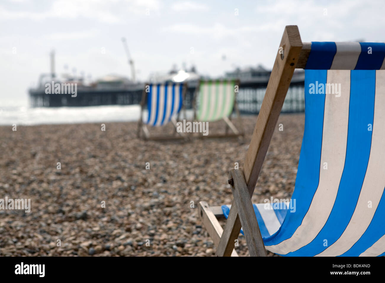 Deck chairs on Brighton beach. - Stock Image
