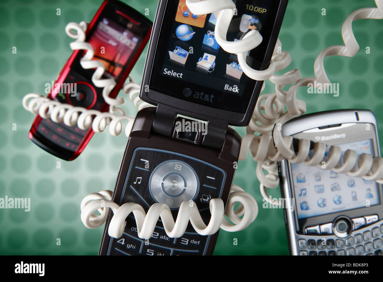 Cell phones floating on green background, wrapped with old fashioned coiled phone cord - Stock Image