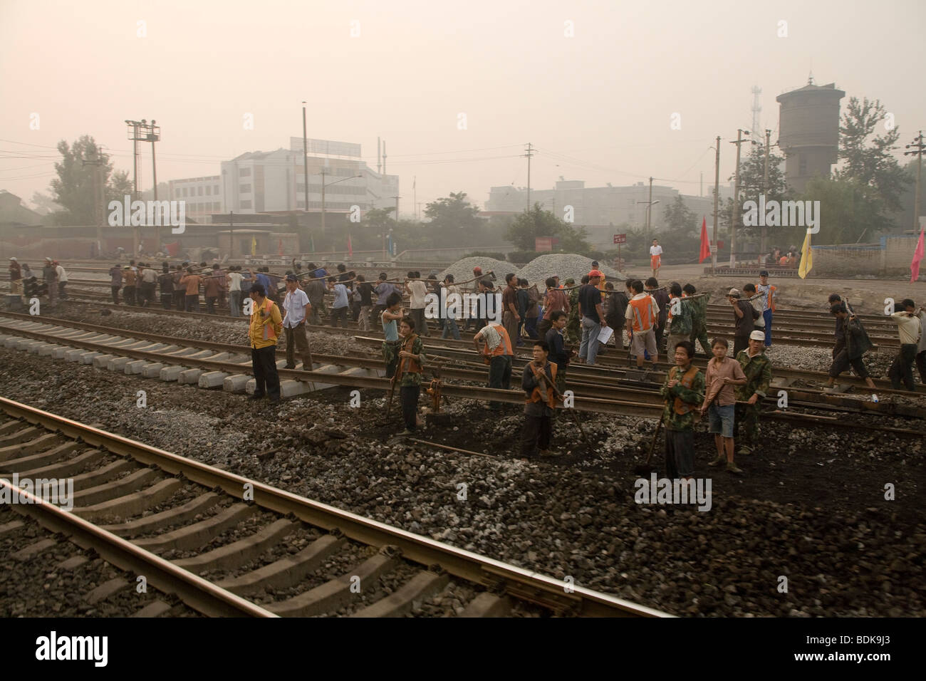 JIEXIU, SHANXI PROVINCE, CHINA - AUGUST 2007: a team of railway workers working in pairs use yokes to lift a steel - Stock Image