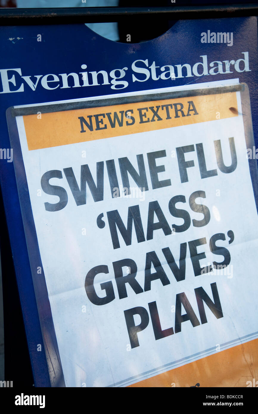 Sign on an Evening Standard newspaper stand warning of Swine Flu Mass Graves. - Stock Image