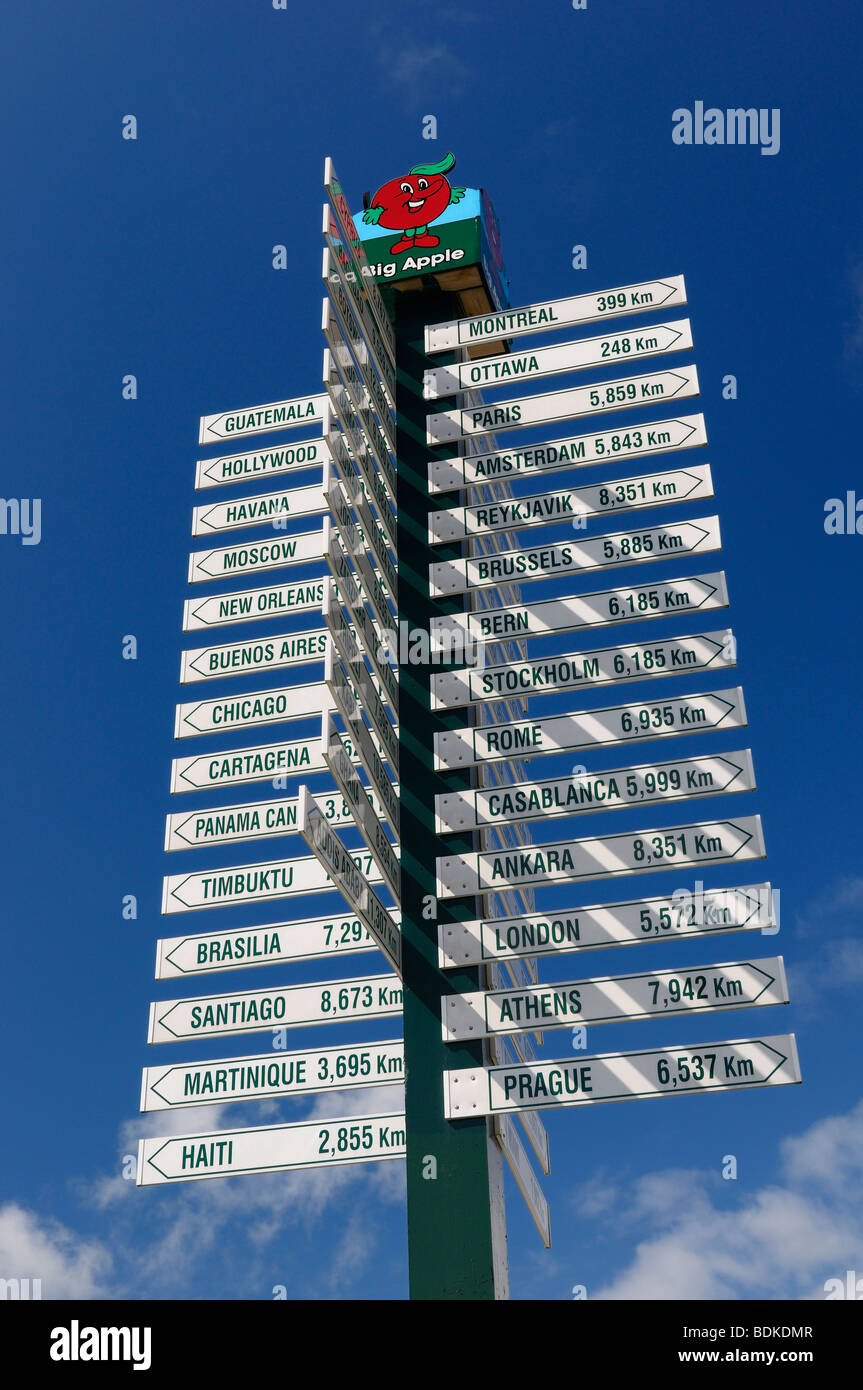 A big apple sign post of distances to world cities in Purdy Corners Colborne Ontario Cramahe Township against blue - Stock Image