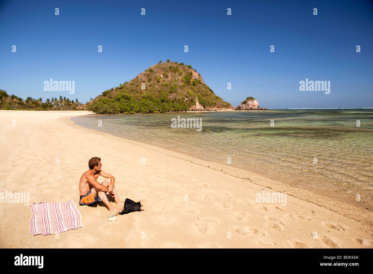 Indonesia, Lombok, Kuta, one solitary male sunbather on the beach - Stock Image