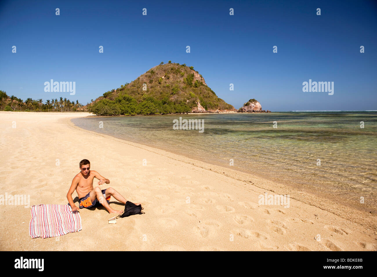 Indonesia, Lombok, Kuta, one solitary male sunbather on the beach Stock Photo