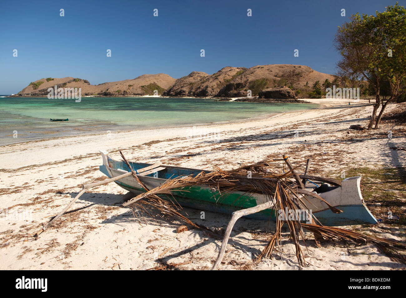 Indonesia, Lombok, Tanjung, beach, fishermen's dugout boat shaded with palm leaves - Stock Image
