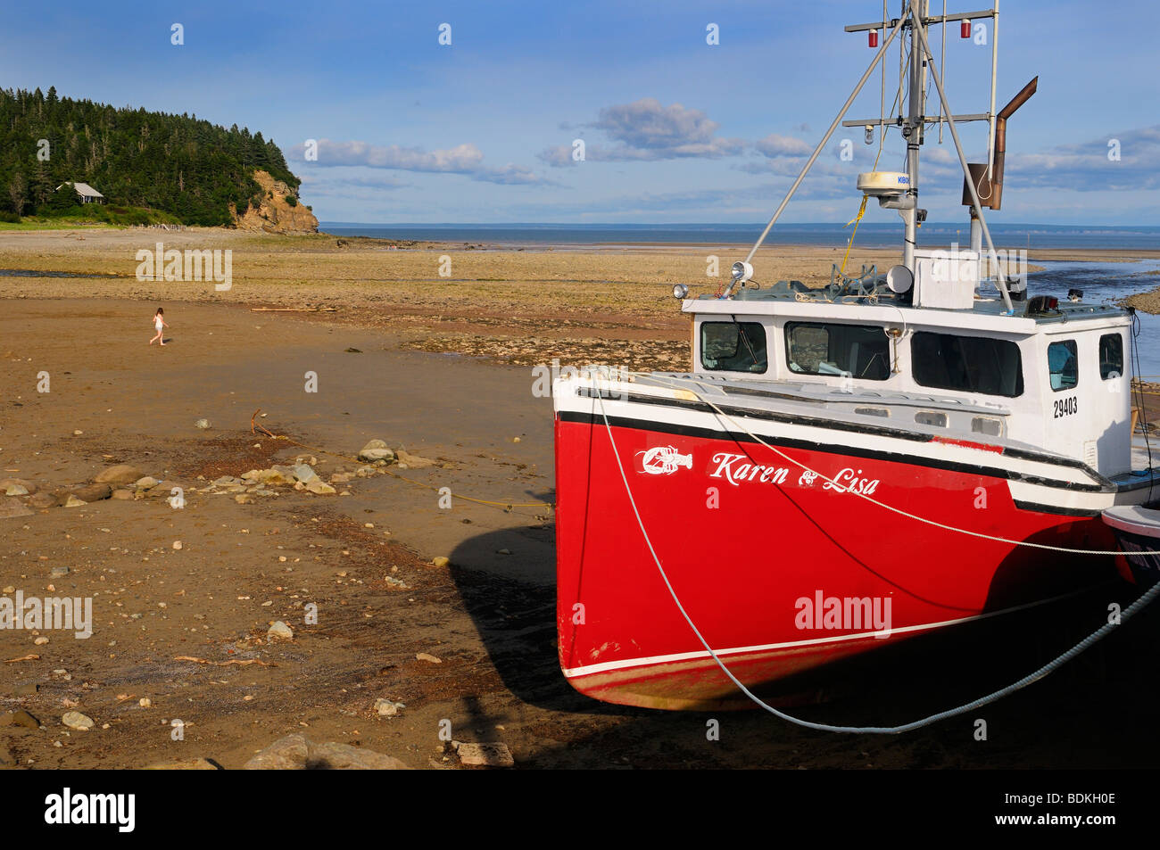 Young girl walking on Ocean floor next to an anchored boat on dry seabed on the Bay of Fundy Alma New Brunswick Stock Photo