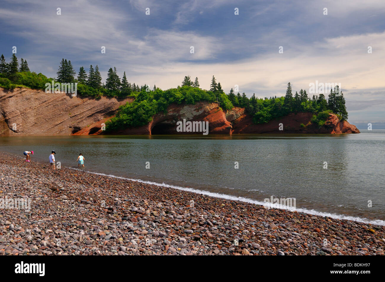 Children playing on pebble beach at sea caves of St Martins New Brunswick at Bay of Fundy high tide - Stock Image