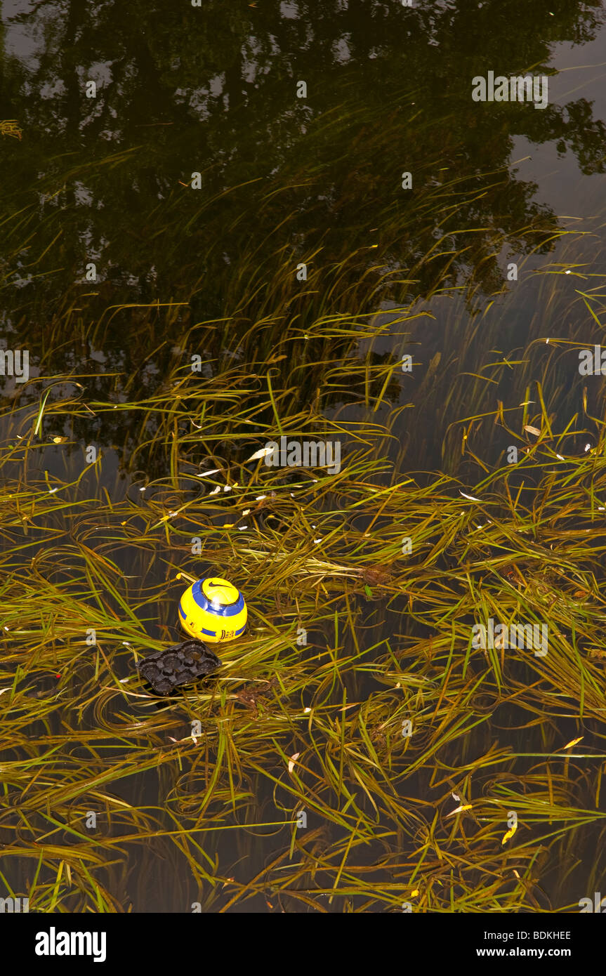 A lost football having been kicked into the river - Stock Image