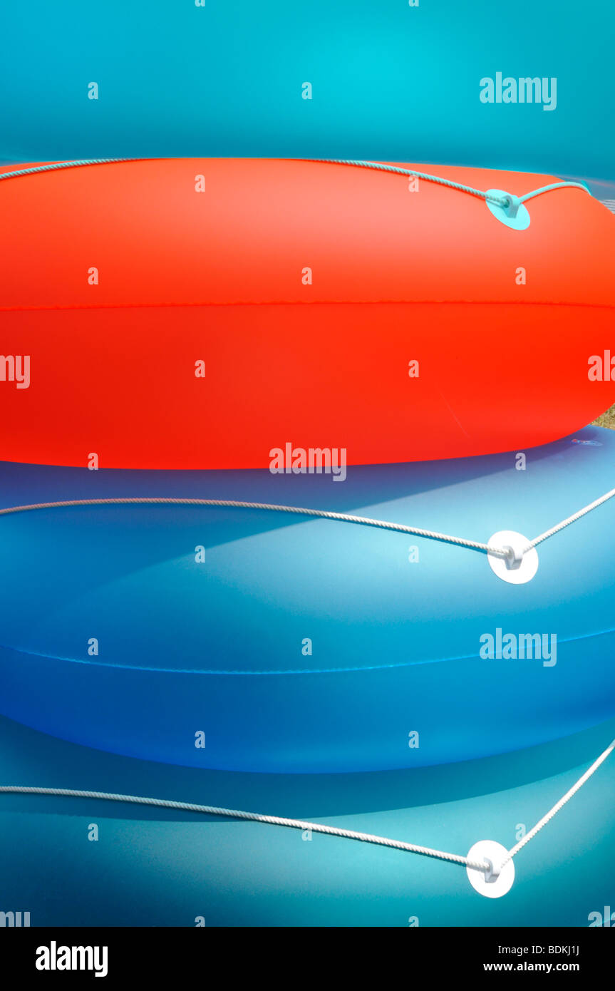 Abstract summer concept shot of colorful inflatable beach flotation rings - Stock Image