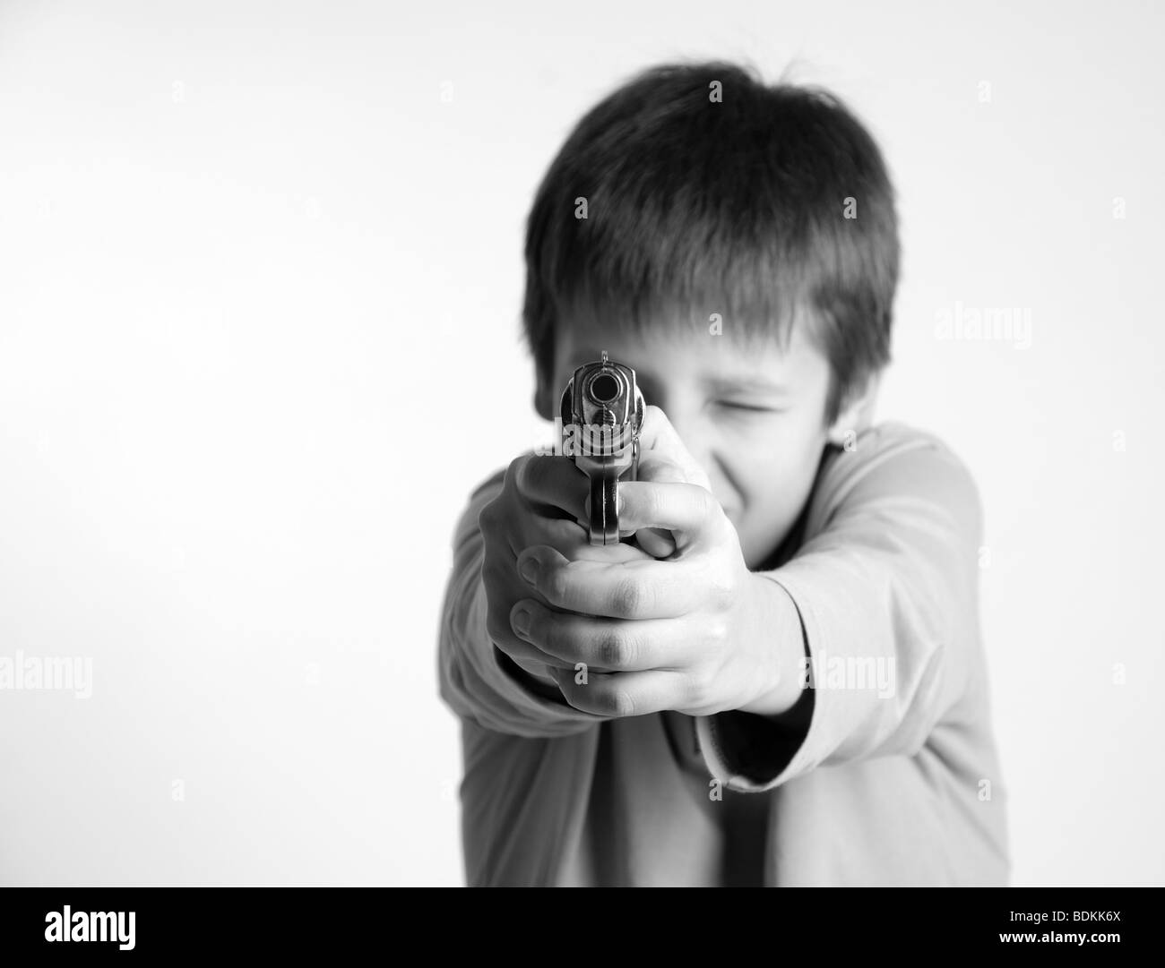 Preteen boy aiming forward a silver pistol, focus on the foreground, shades of gray, copy space - Stock Image