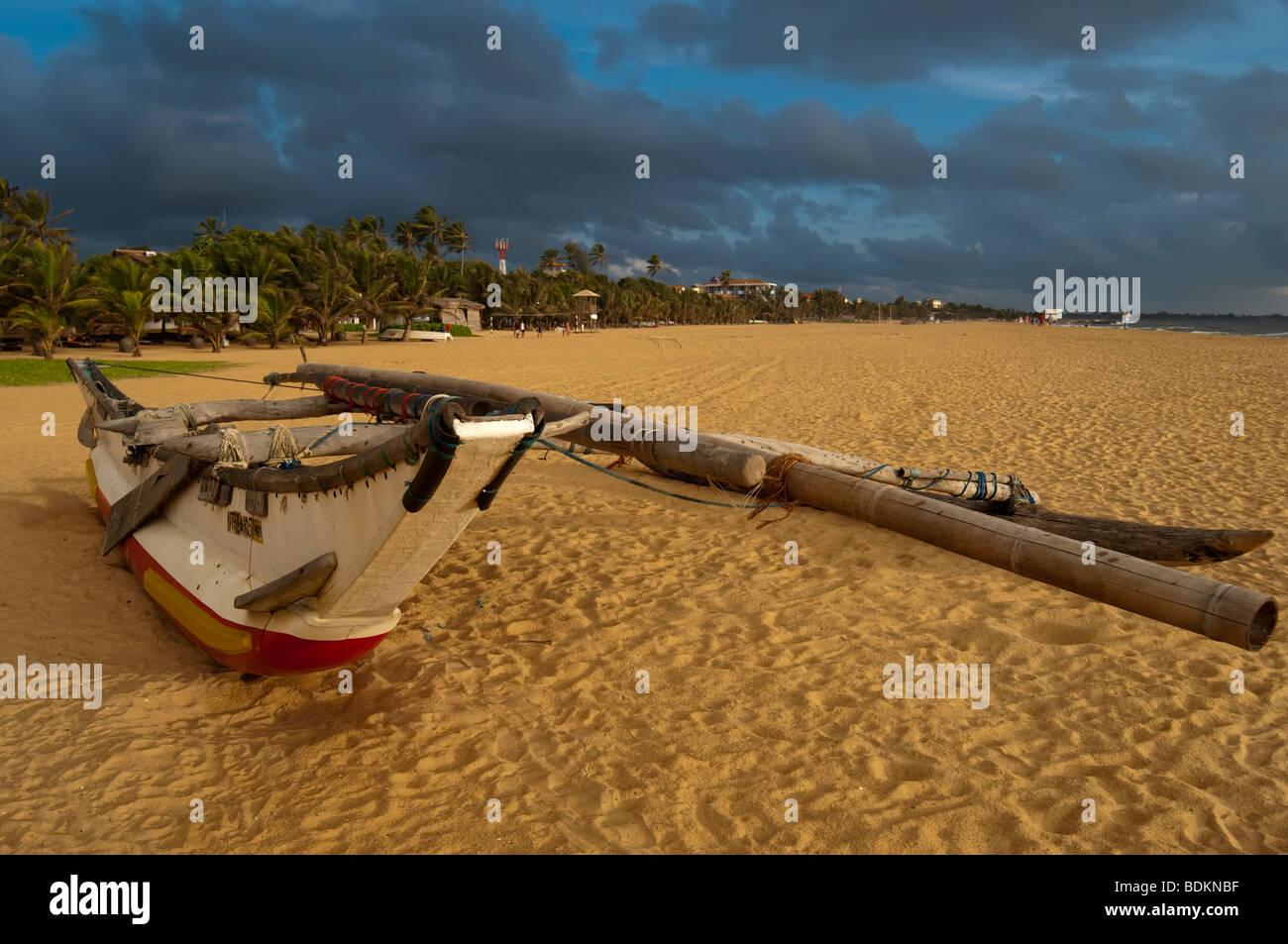 Traditional Fishing Boat Sri Lanka on beach rain storm clouds in background Stock Photo