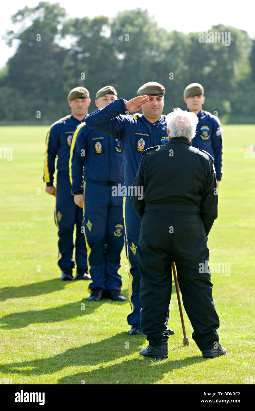 Former RAF serviceman, eighty-eight-year-old Tom Lackey takes the salute from members of the Red Devils parachute - Stock Image