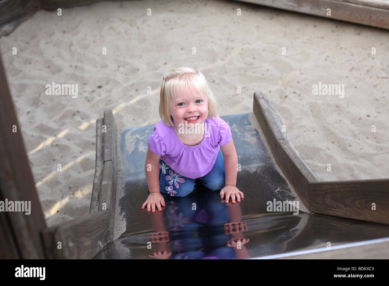 Young girl on slide smiling - Stock Image