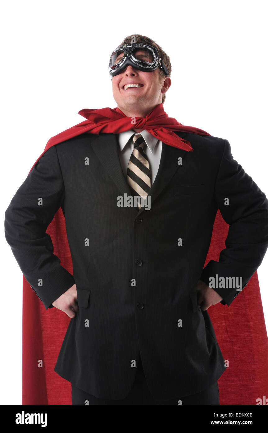 Businessman with red cape and goggles smiling confidently - Stock Image
