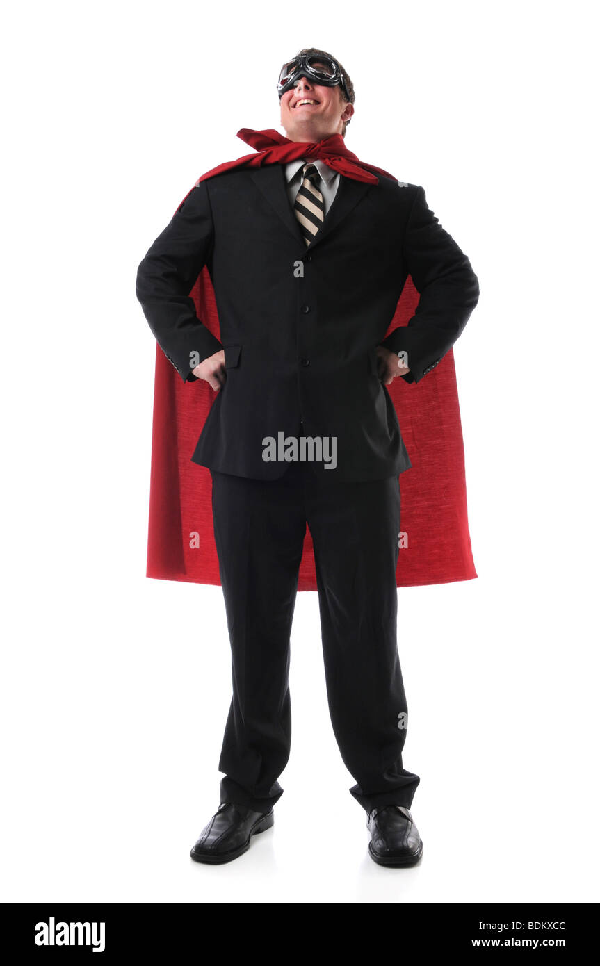 Man dressed in suit, cape and goggles standing confidently - Stock Image