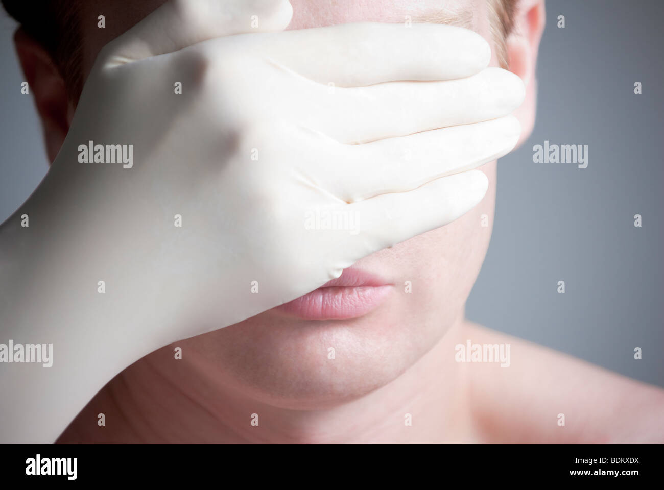 Man covering his eyes while wearing a white medical glove - Stock Image