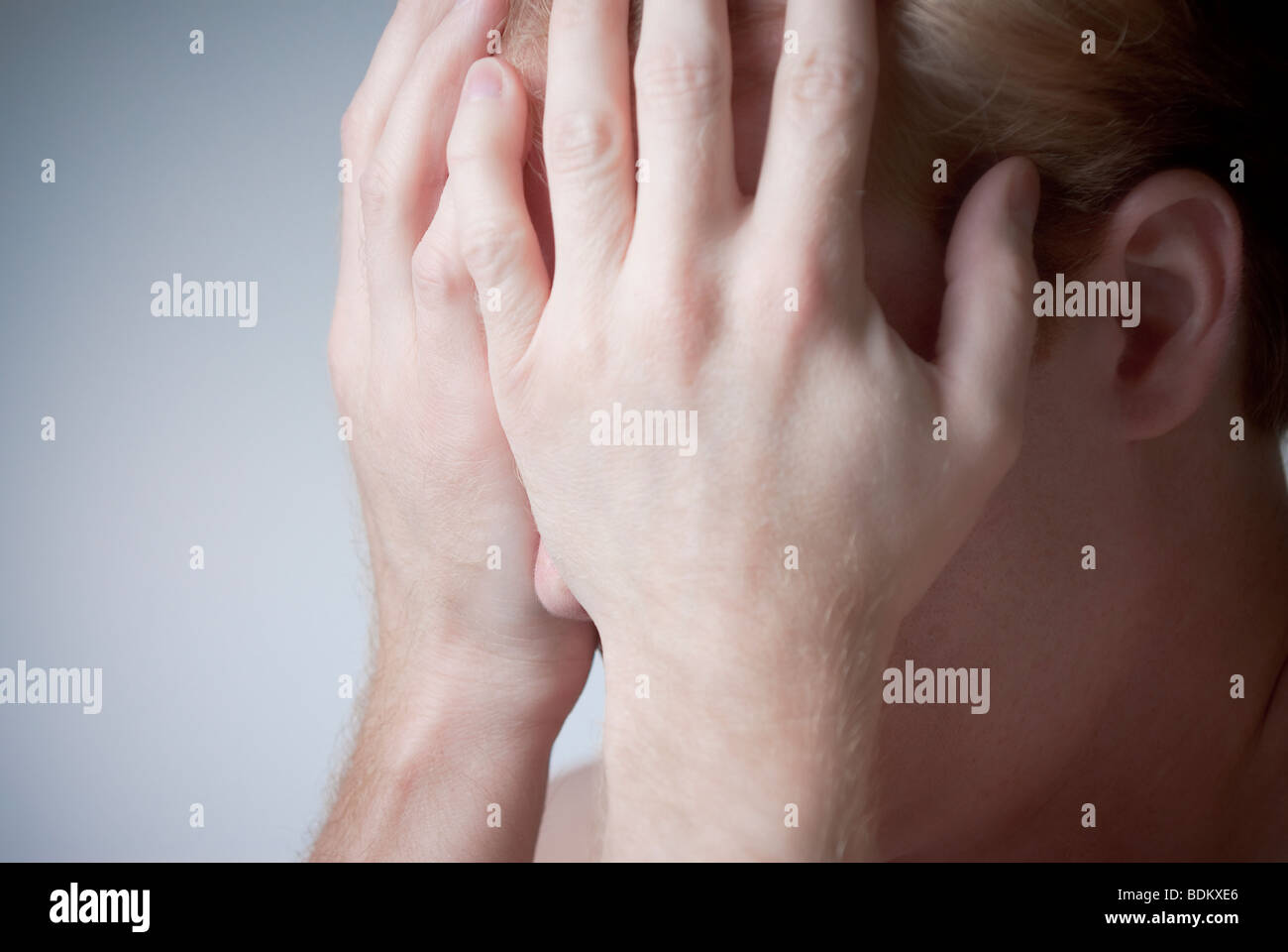 Man holding his head in his hands - Stock Image
