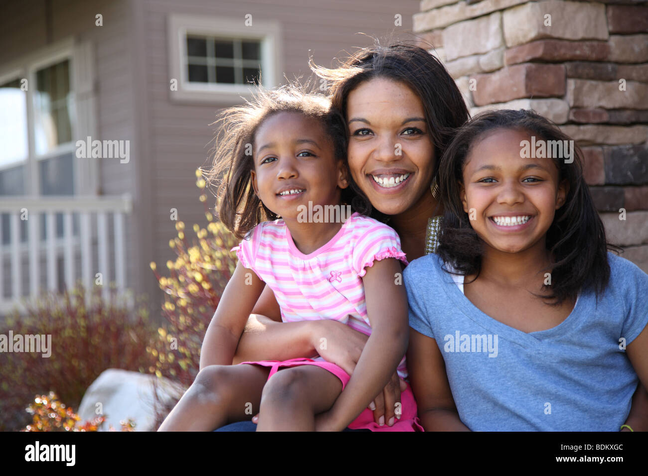 Portrait of mother and daughters sitting on porch - Stock Image