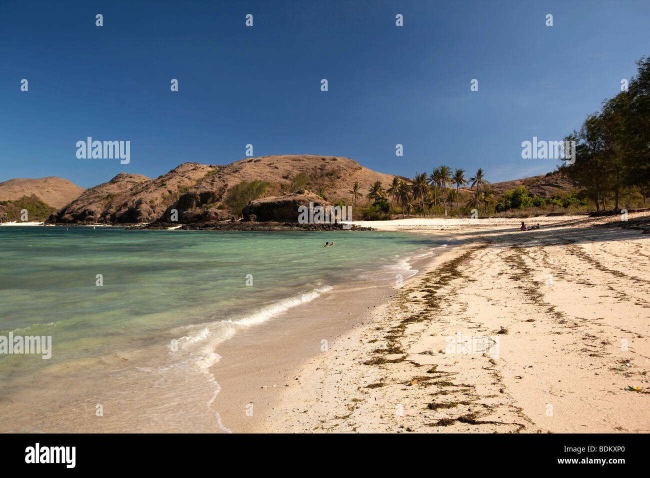 Indonesia, Lombok, Tanjung, visitors enjoying almost empty idyllic tropical beach - Stock Image