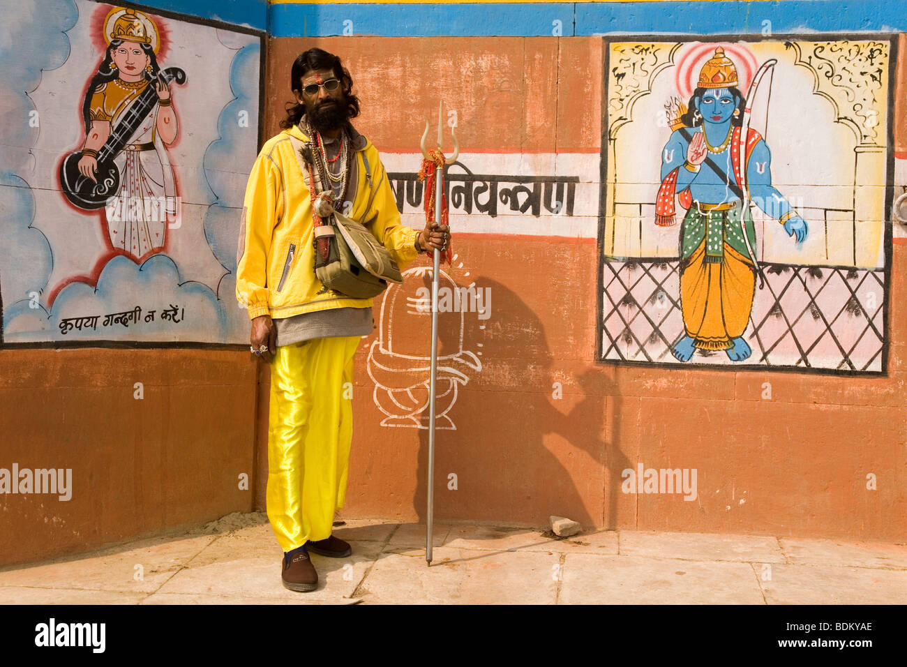 A Sadhu in the Indian city of Varanasi (Benares). He stands in front of paintings of deities on a brick wall. - Stock Image