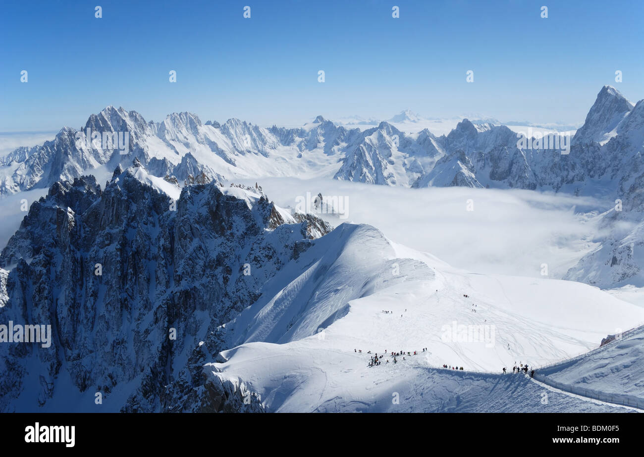 Snow slope with mountain-skiers against blue sky and steep peaks of the Alps, Mont Blanc, France - Stock Image