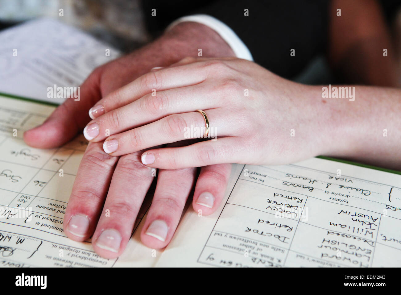 Closeup of bride and groom hands on marriage register during signing ...