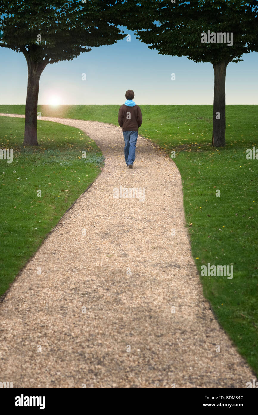 A boy walking along a winding path between two trees towards a setting sun - Stock Image