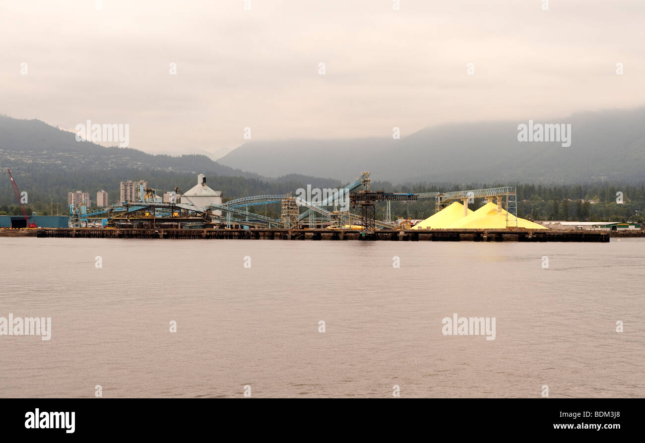 Burrard Inlet and Suphur stockpiles at Vancouver Wharves, North Vancouver, BC, Canada. - Stock Image