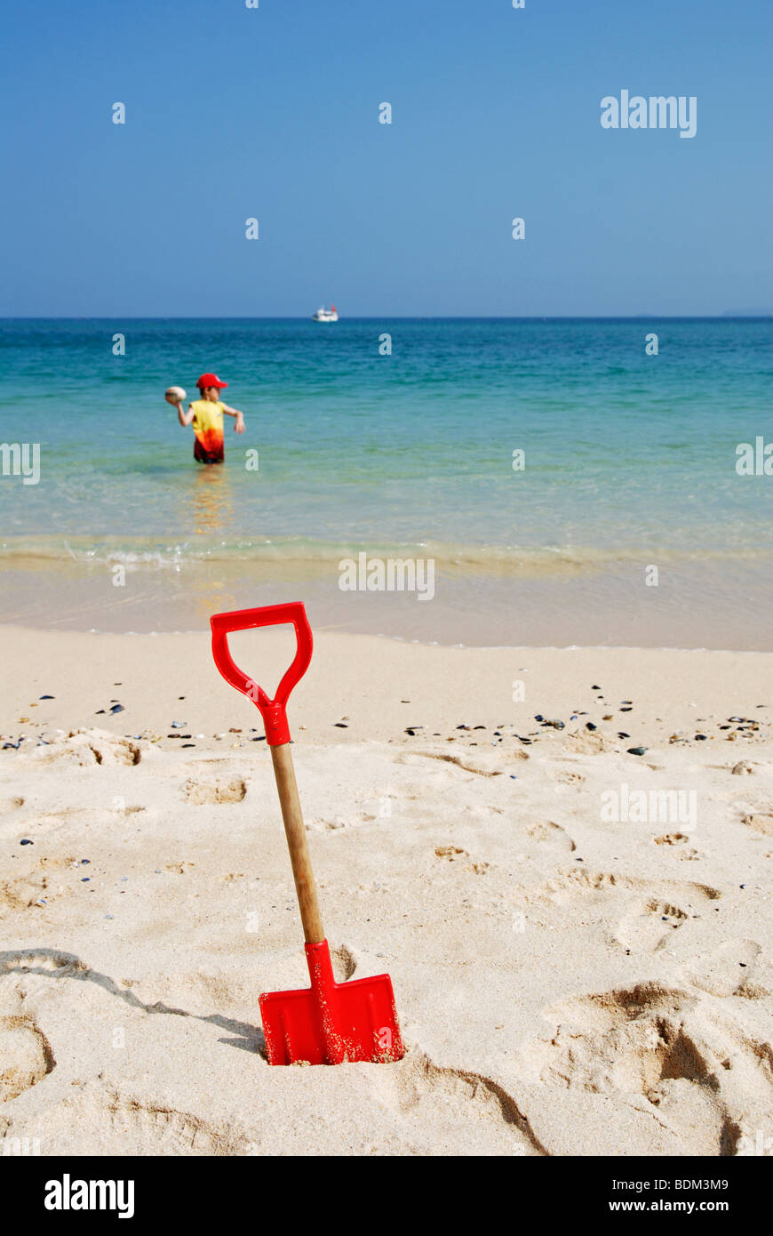 a red spade in the sand on the beach at st.ives in cornwall, uk - Stock Image