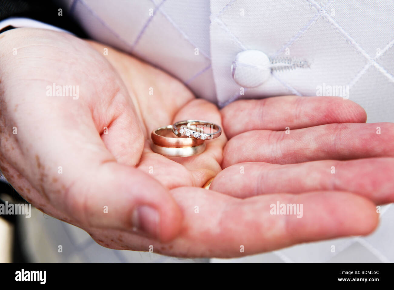 Close up of groom holding new wedding bands rings in palm of hand on ...
