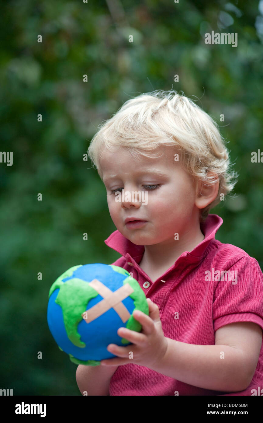 Young boy holding a model of a sick planet Earth with a Band Aid attached - Stock Image