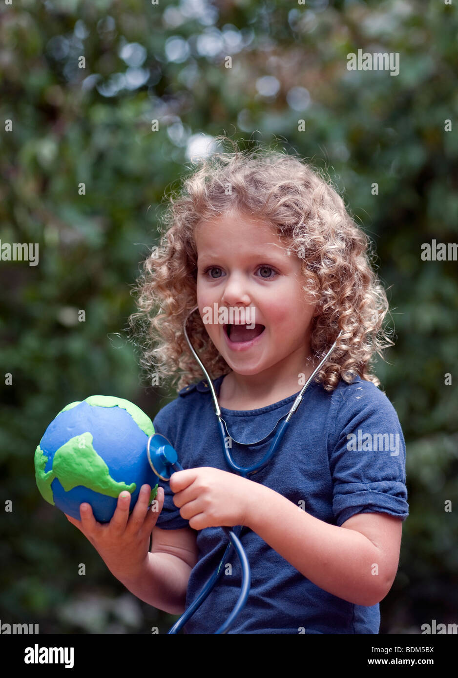 Young child holding a model of planet Earth and checking its health with a stethoscope - Stock Image