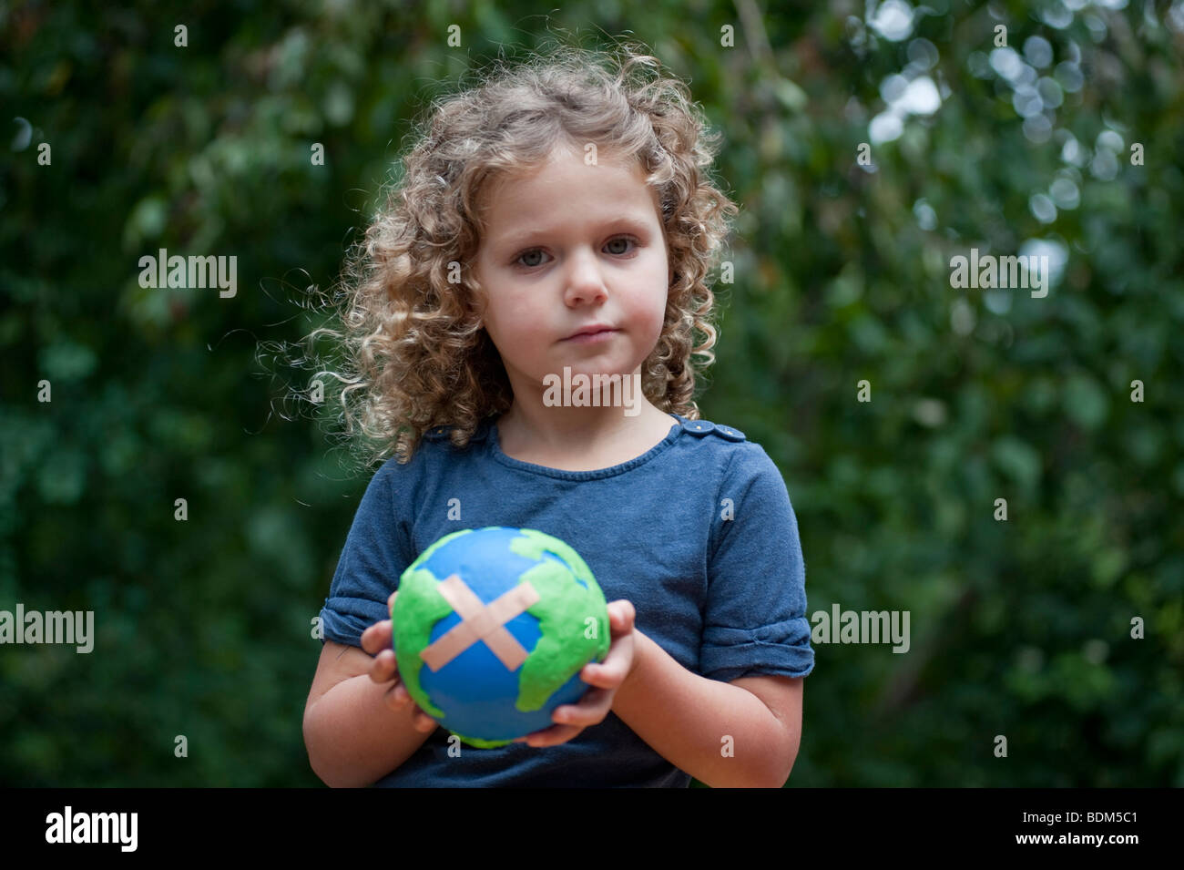 Young girl holding a model of a sick  planet Earth with a Band Aid attached - Stock Image