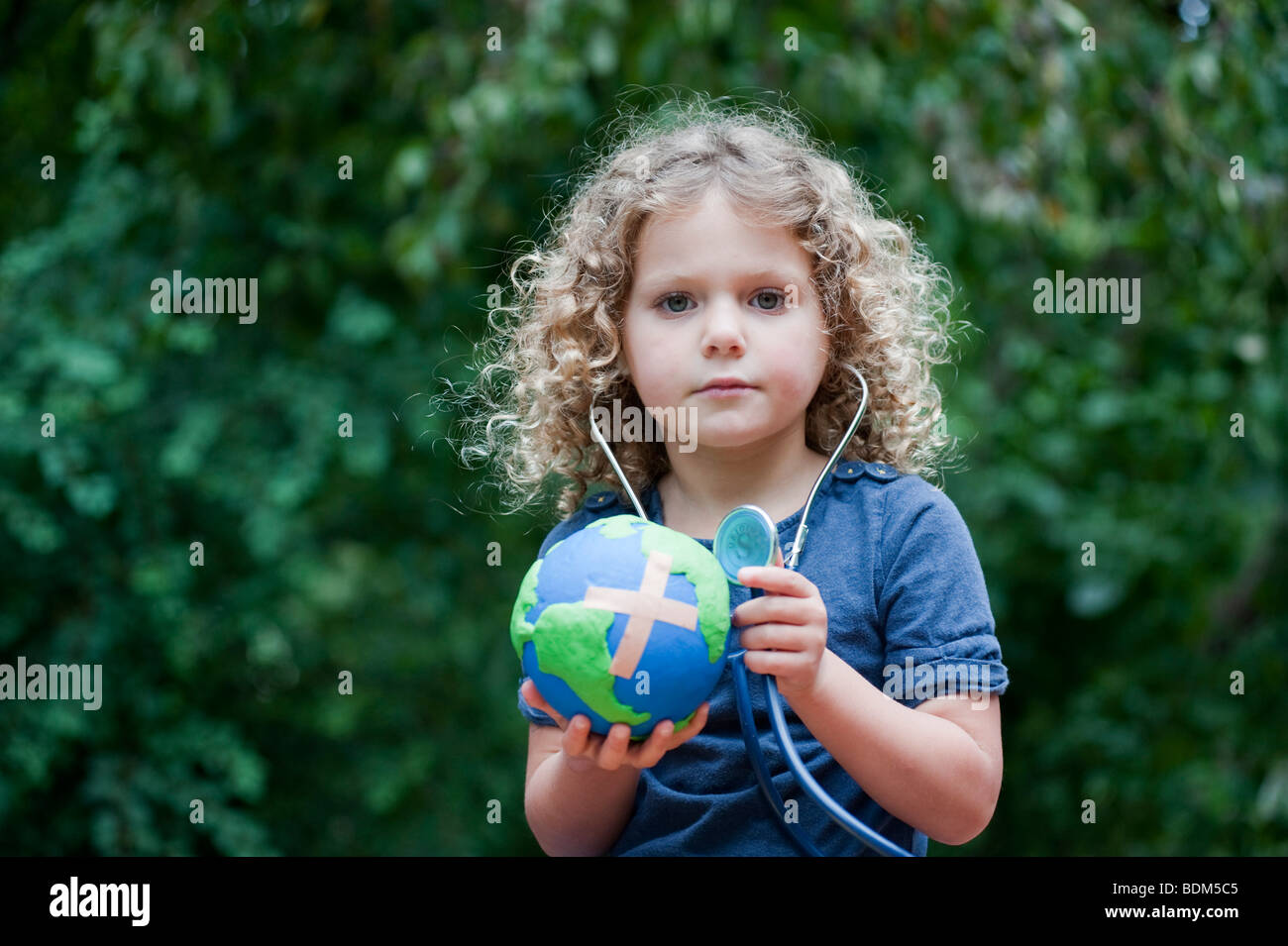 Young girl holding a model of a sick  planet Earth with a Band Aid attached and checking its health with a stethoscope - Stock Image
