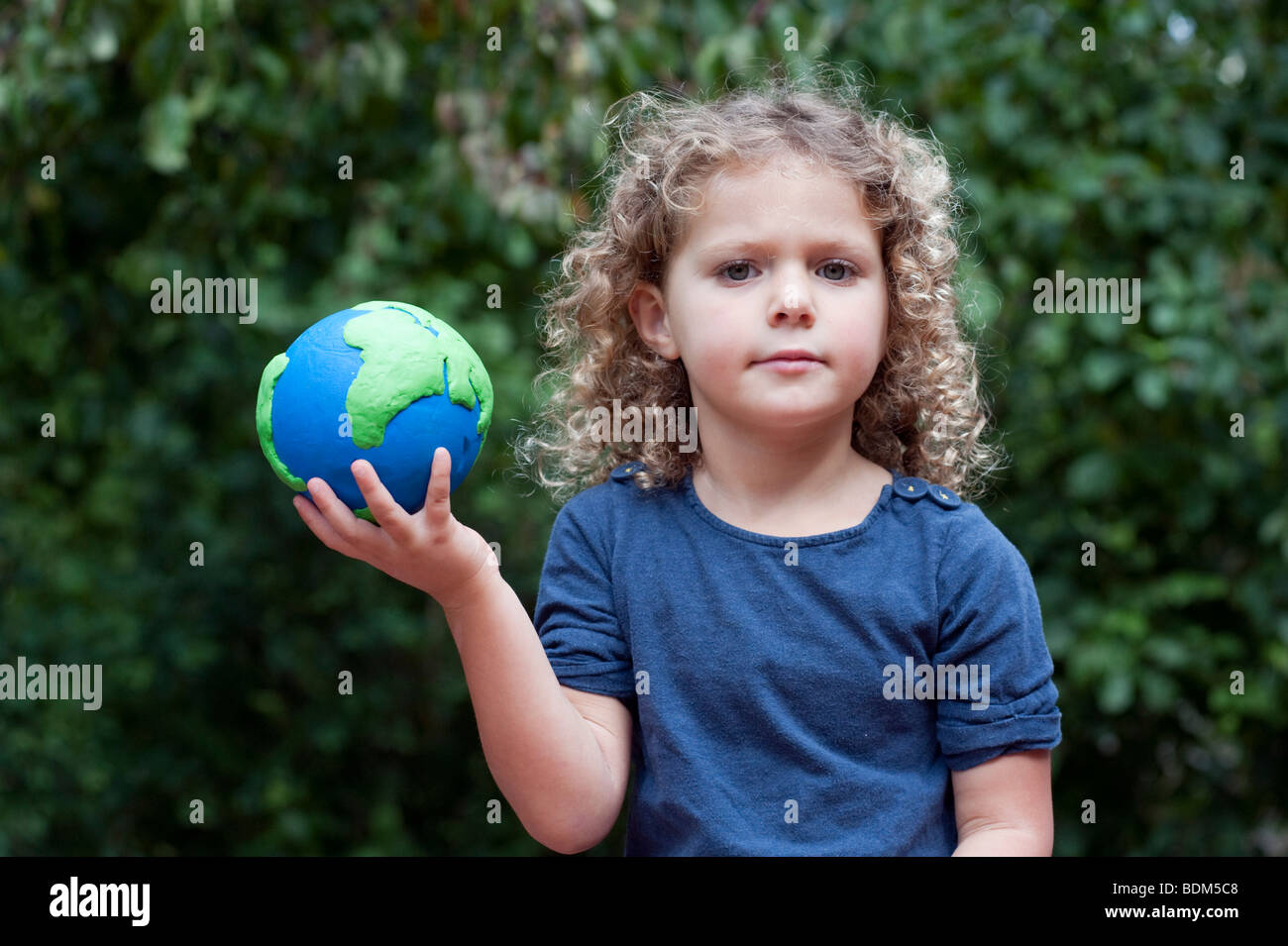Young girl holding a model of The Earth - Stock Image