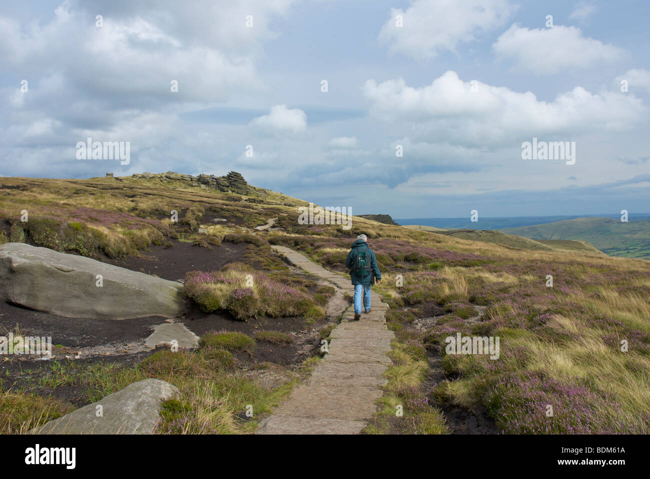 Walker striding towards Pym Chair, Kinder Scout, near Edale, Peak National Park, Derbyshire, England UK - Stock Image