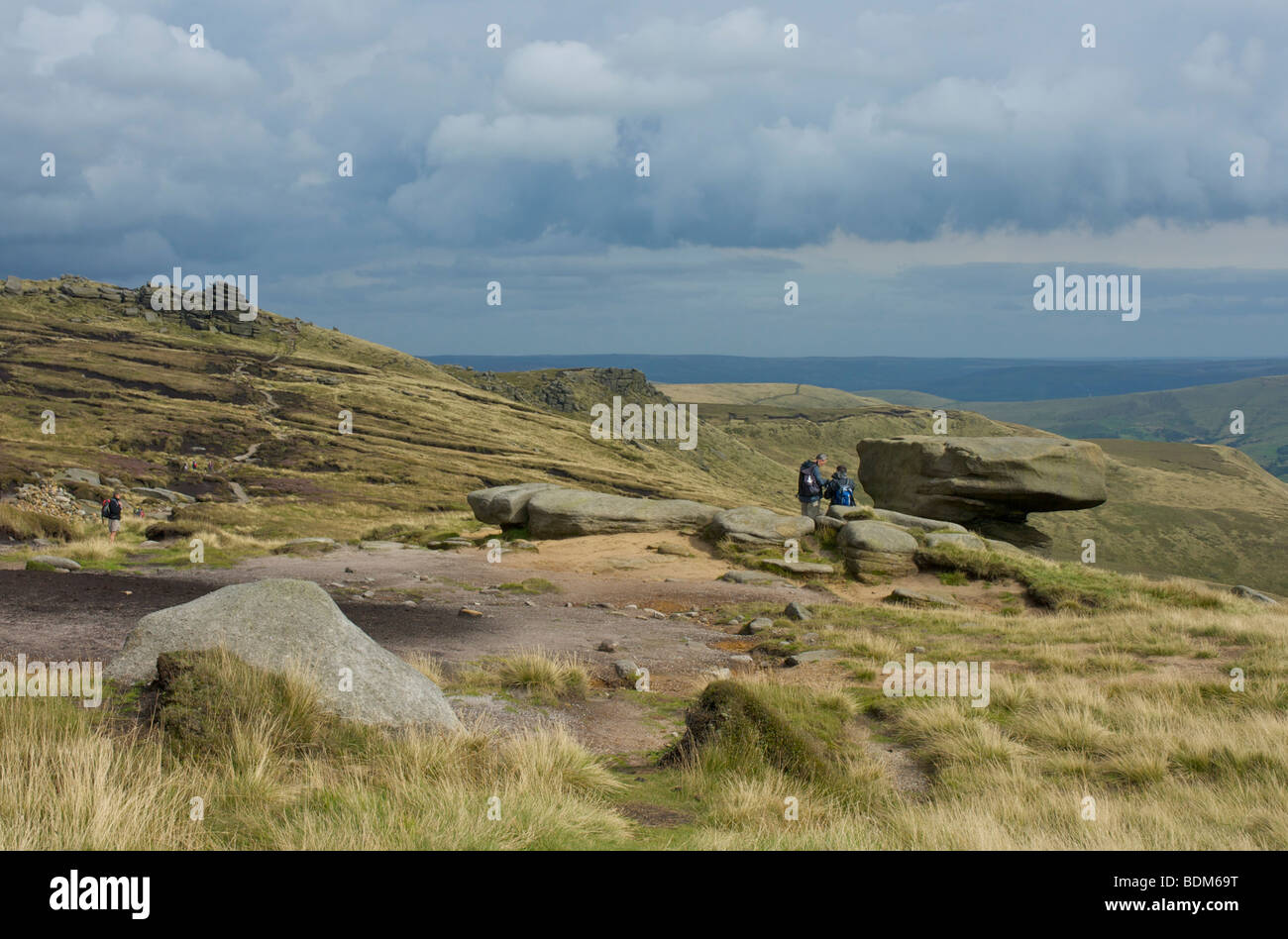 Two walkers at the Noe Stool on Kinder Scout, near Edale, Peak National Park, Derbyshire, England UK - Stock Image
