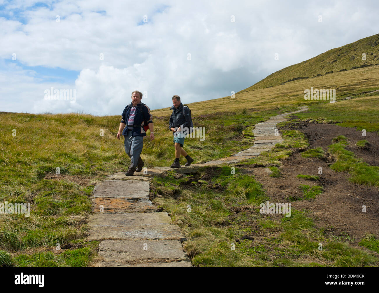 Two walkers on new flagged section of the Pennine Way path, Kinder Scout, near Edale, Peak National Park, Derbyshire, Stock Photo