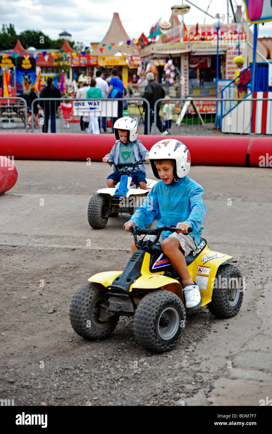 little boys riding quad bikes at the funfair in southport,lancashire,uk - Stock Image
