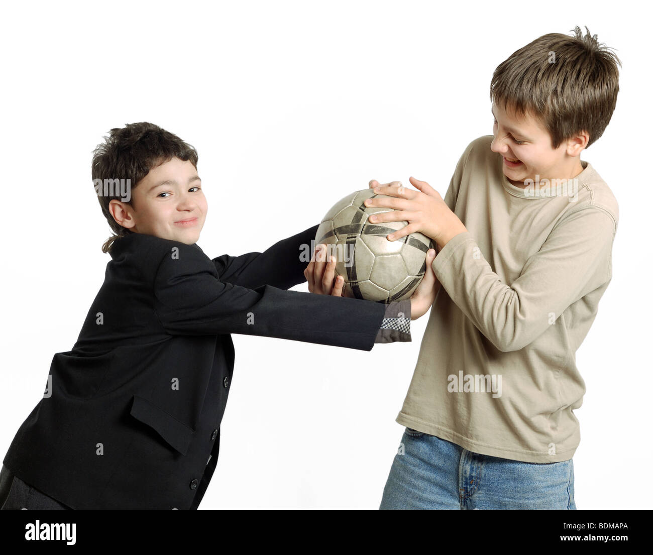 Two preteen boys pull out ball with each other. Side view. The children are smiling. Stock Photo