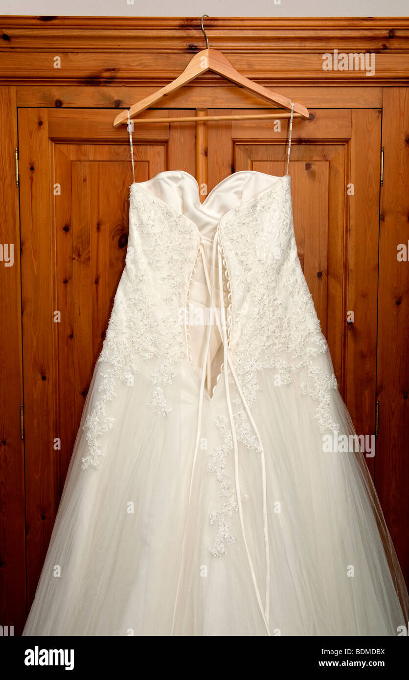 White wedding dress hanging on the outside of a wardrobe - Stock Image