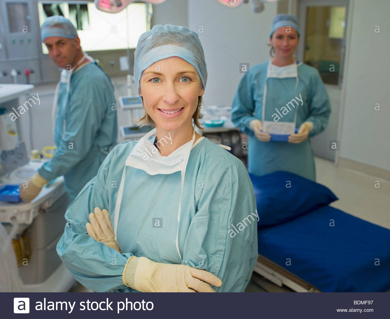Surgeons preparing for surgery in operating room - Stock Image
