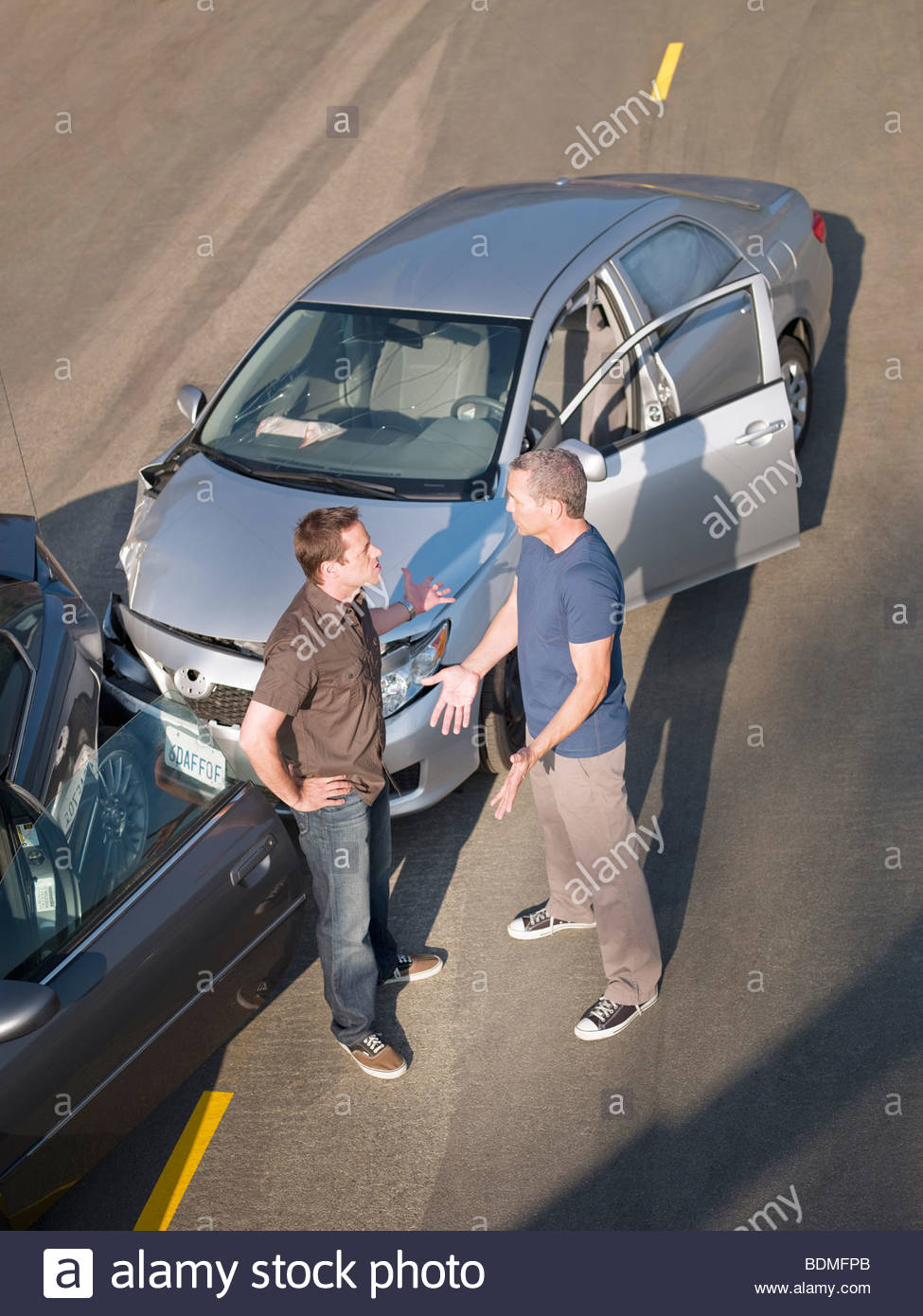 Two men arguing about damage in car collision - Stock Image