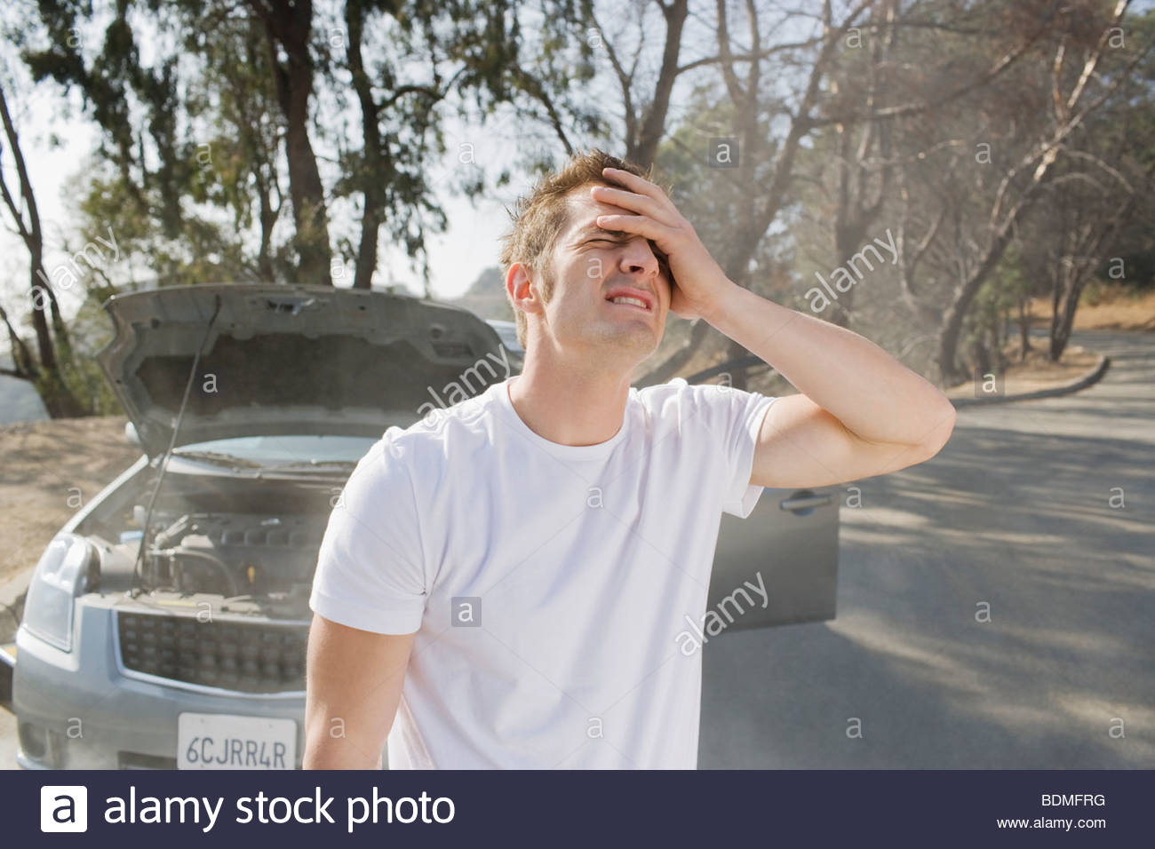 Frustrated man standing near broken down car - Stock Image