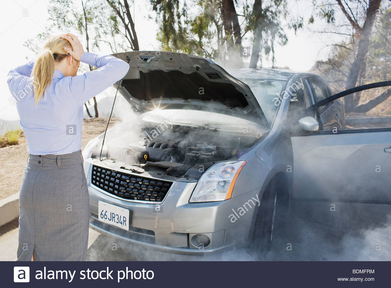 Frustrated woman looking at smoking car engine - Stock Image
