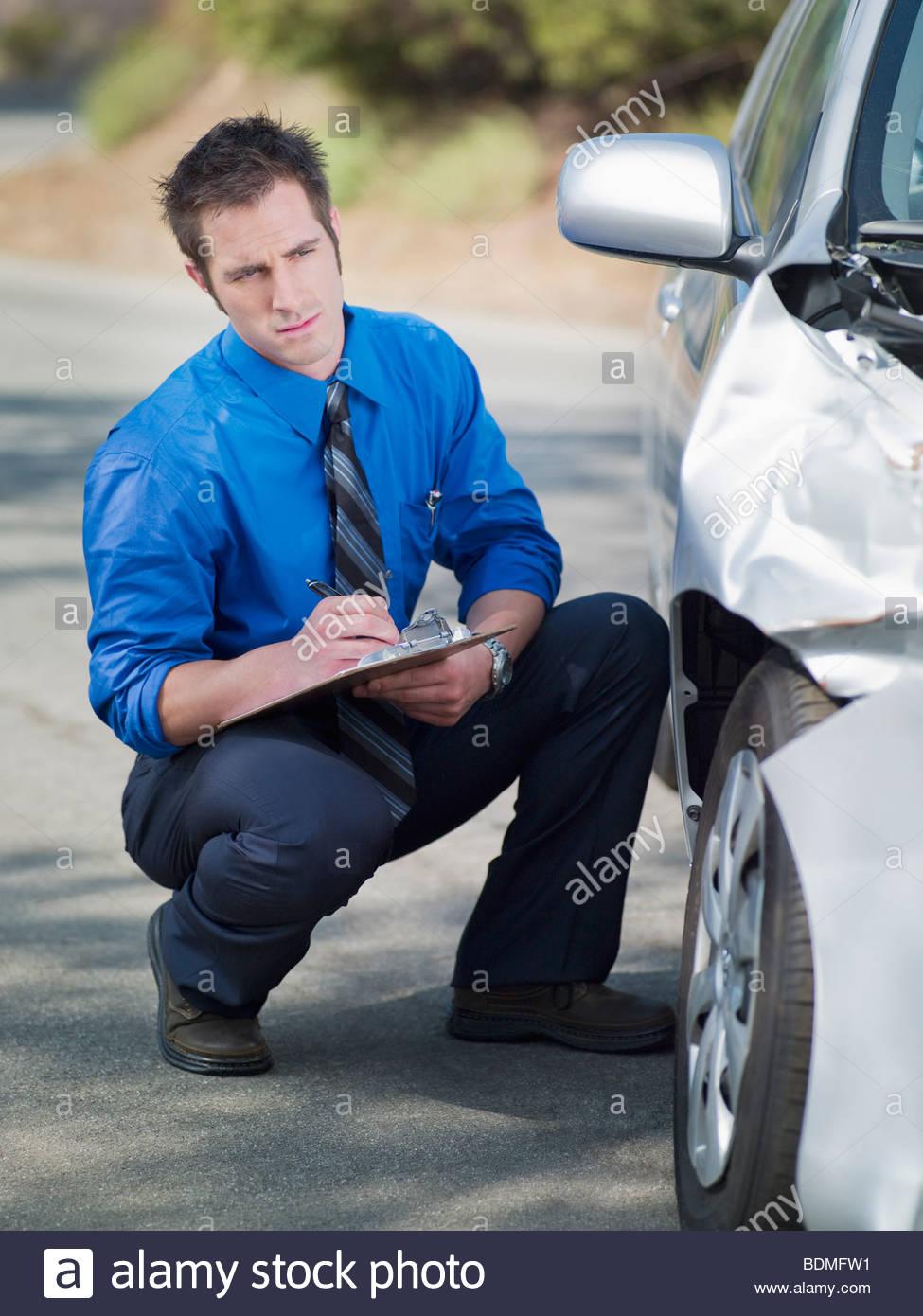 Insurance adjuster looking at damaged car - Stock Image